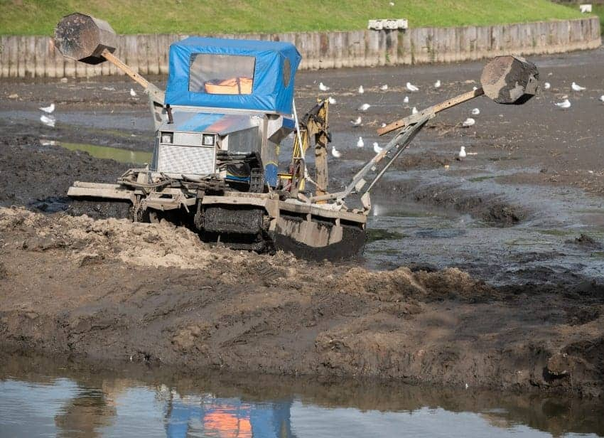 tractor dredging a lake full of mud